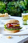 A hamburger and a sesame seed bun with lettuce, mustard, ketchup, tomatoes and red onions on a picnic table with beer and chips