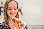 A young woman with a white sausage hot dog