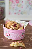 Biscuits with dried rose petals in biscuit tin with pattern of roses