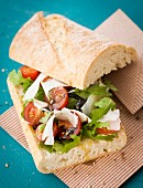 Ciabatta sandwich with rocket, tomatoes and Parmesan cheese
