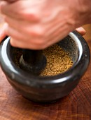 A spice mixture being ground in a mortar