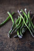 Green asparagus on a dark wooden surface