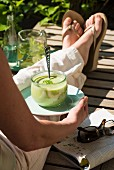 A woman with herb soup on a garden lounger