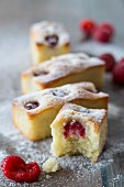 Financiers with raspberries and icing sugar, one with a bite taken out