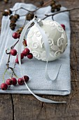 A Christmas tree bauble and hawthorn berries