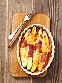 Gratinated courgette with ham and cheese in tomato sauce