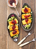 Breaded cheese with cranberry jam and a mixed leaf salad