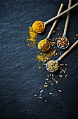 Curry powder, turmeric, cumin seeds and coriander seeds on ceramic spoons