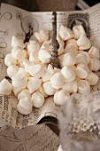 White meringues on vintage-style paper on cake stand