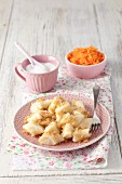 Leniwe (Polish quark dumplings) with buttered crumbs, sugar and a carrot salad