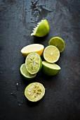 Lime halves, some juiced, on a black surface