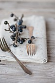 Silver forks and a napkin decorated with a sprig of sloes