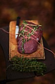 Steak with herbs being prepared for grilling on a chopping board