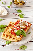 Spicy potato waffles with tomatoes, olives and feta cheese