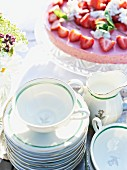 A strawberry tart and teacups on a garden table