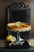 lemon tart on a glass cake stand with fresh lemons