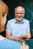 A man and a woman drinking cherry punch in front of a house
