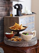 Tortilla chips with a bean dip and a sour cream dip on a wooden board