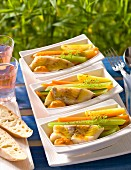 Cod fillets with saffron and vegetables on a table outside