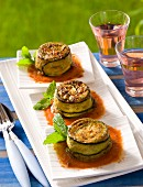 Minced lamb cakes wrapped in courgette on a table outside