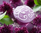 A purple cupcake decorated with a filigree pattern