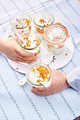 Children holding two glasses of Eton Mess with apricots