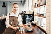 A barista at the counter in a coffee shop