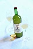 A bottle of 'Gravensteiner' apple juice, glasses of juice and an apple quarter