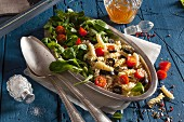 Mediterranean pasta salad with vegetables, tomatoes, black olives and sesame seeds