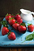 Fresh strawberries in a bowl and a jug of cream on a chopping board