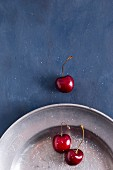 Sweet cherries on a pewter plater sprinkled with sugar