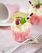 Cupcakes decorated with white chocolate cream, kiwis, raspberries and chocolate cigars