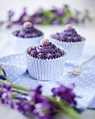 Cupcakes decorated with purple cream and jelly sweets