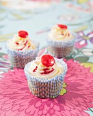 Cupcakes with strawberry syrup and sweets