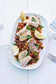 Rosefish on a bed of couscous with tomatoes and capers