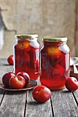 Jars of preserved red plums with cinnamon and honey