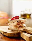Four slices of olive bread with red chilli on a wooden board