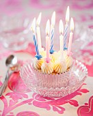 A cupcake with vanilla butter cream and birthday candles