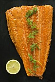 Smoked salmon with dill on a black surface (seen from above)