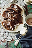 Chocolate crêpes with marshmallows, chocolate pieces and chocolate cream