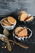 Almond flour and honey biscuits in homemade earthenware cases with golden-handled spoons on a black surface