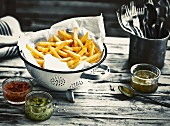 Chips in a colander lined with kitchen paper