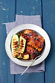 Barbecued chicken bits with grilled courgette and pomegranate seeds