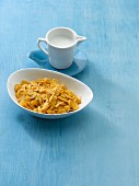 A bowl of cornflakes with a jug of milk