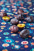 Damsons on a blue, floral patterned tablecloth