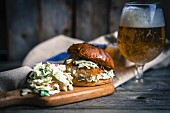 A rustic fish burger with coleslaw and beer