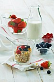 A healthy breakfast: muesli with fresh fruit and milk, strawberries, raspberries, blueberries on a wooden table