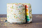 A rainbow layer cake with white frosting