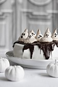 Halloween cake topped with meringue ghosts