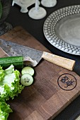 Chopping board engraved with owl, sharpened knife and vegetables